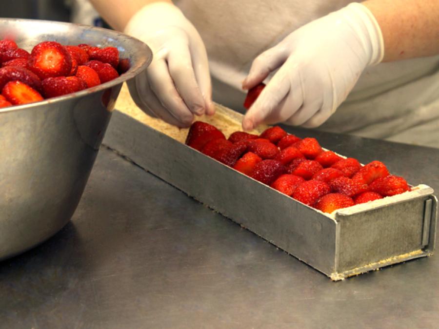 Erdbeerschnitte wird mit Erdbeeren belegt